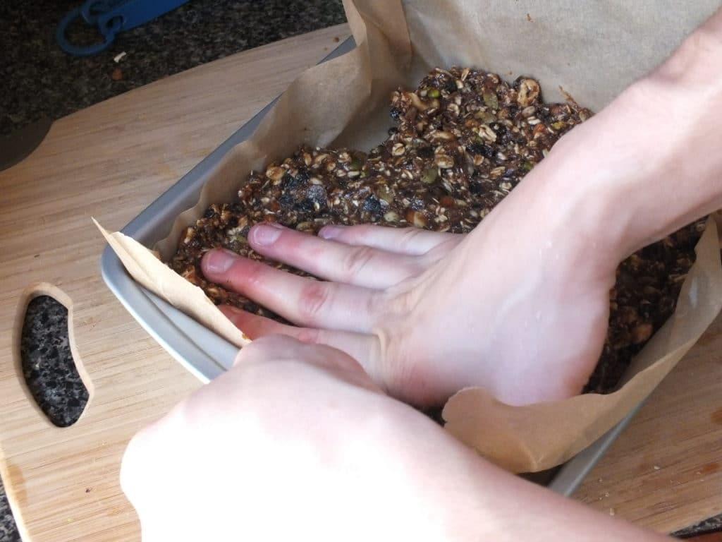 Raw Energy Bars Baking Tray Hand Pressing Mix
