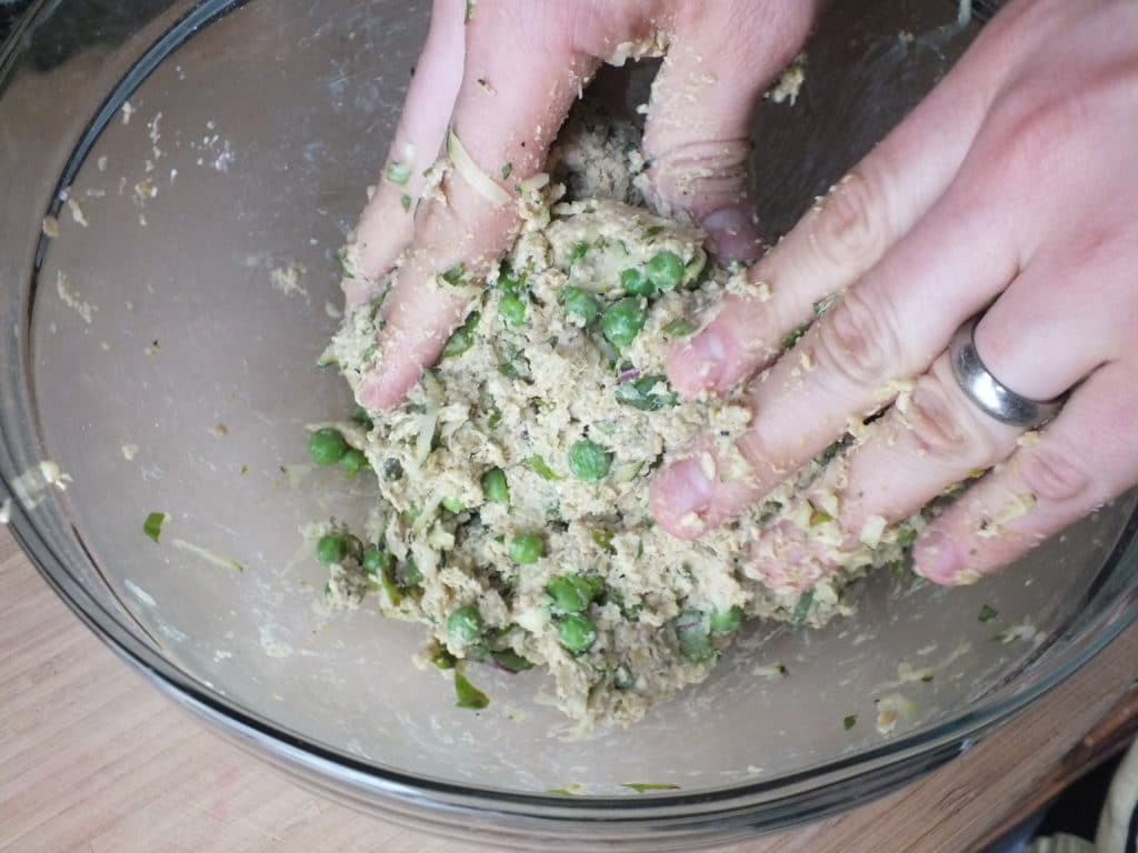 Hands Mixing Savory Quinoa Cake in Bowl