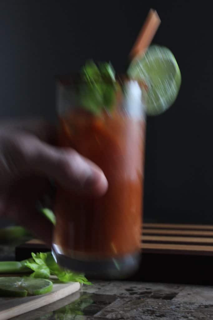Hand Holding Glass of Chili Mango Bloody Mary Blurred Image