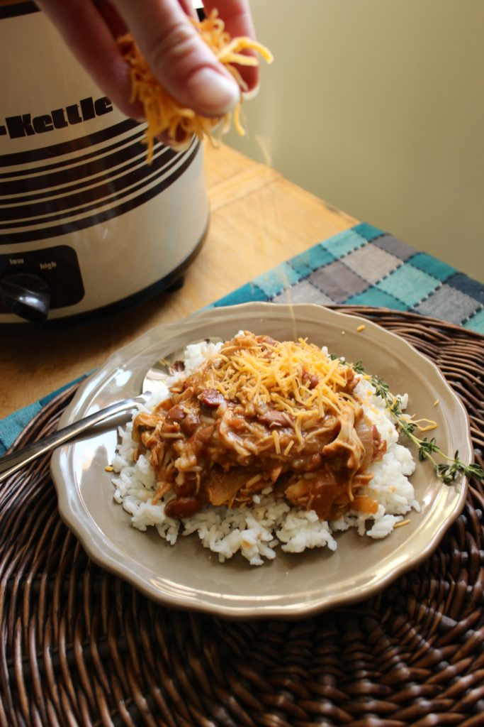 Slow Cooker Chicken and Beans on Plate Sprinkling Cheese