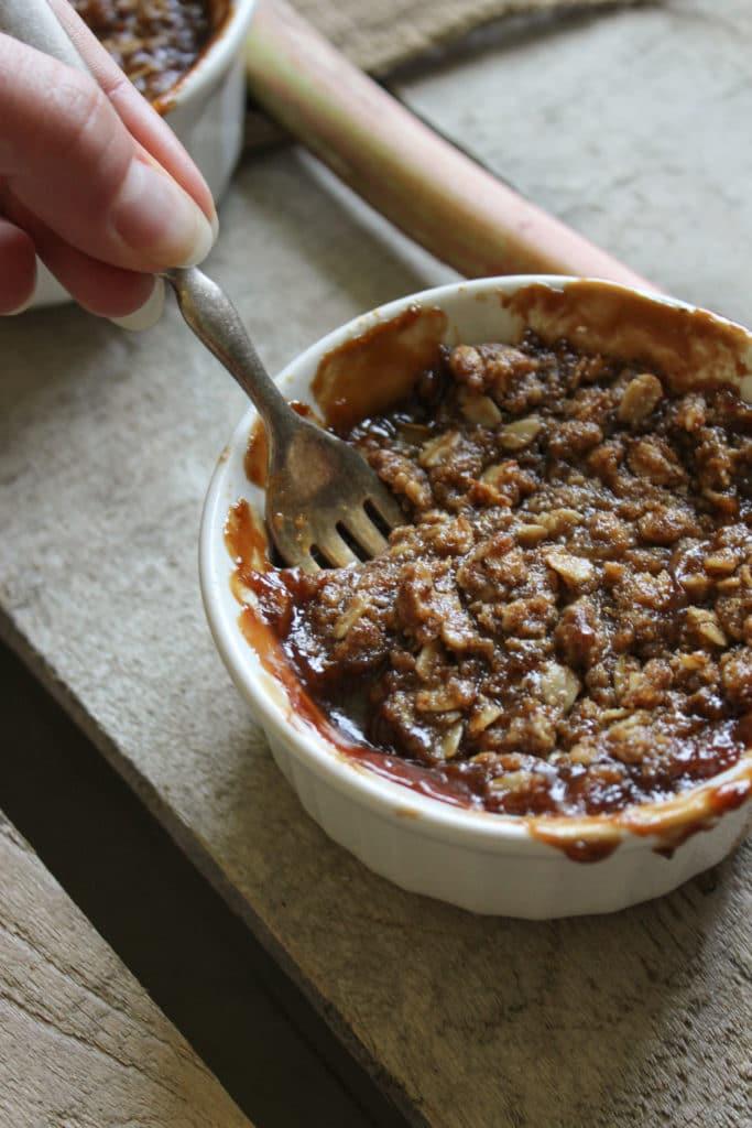 Gluten Free Rhubarb Rum Crisps in Bowl Hand Holding Fork