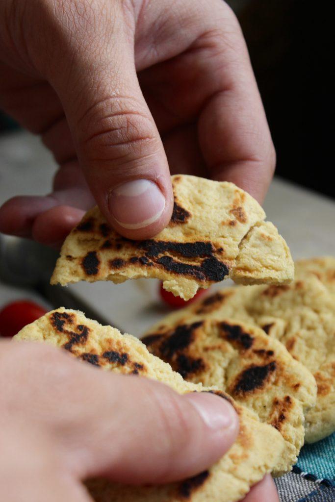 Hands Breaking Naan Bread