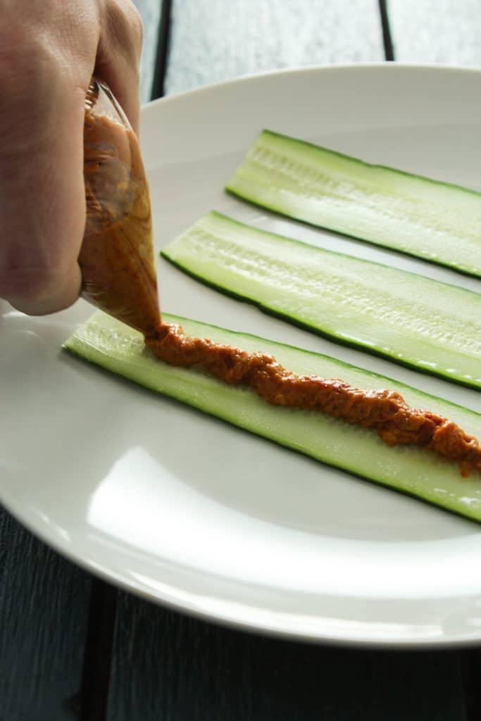Hand Squeezing Sundried Tomato Pesto onto Cucumber