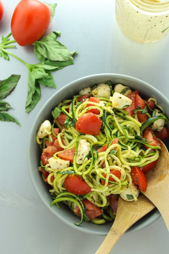 Zucchini Caprese Salad in bowl with wooden spoons Tomatoes