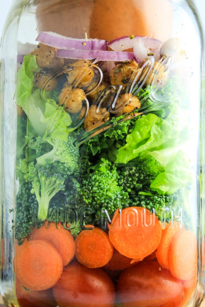 "Mason Jar Salads with Kalamata Dressing – These are perfect for taking to work or traveling. It has layers of tomatoes, carrots, broccoli, greens and chickpea ""croutons."" The creamy kalamata dressing is made with vegan coconutmilk yogurt."