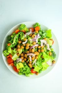 """Mason Jar Salads with Kalamata Dressing – These are perfect for taking to work or traveling. It has layers of tomatoes, carrots, broccoli, greens and chickpea """"croutons."""" The creamy kalamata dressing is made with vegan coconutmilk yogurt."""