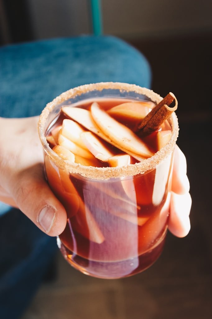 Hand Holding Glass of Red Wine Apple Cider Sangria