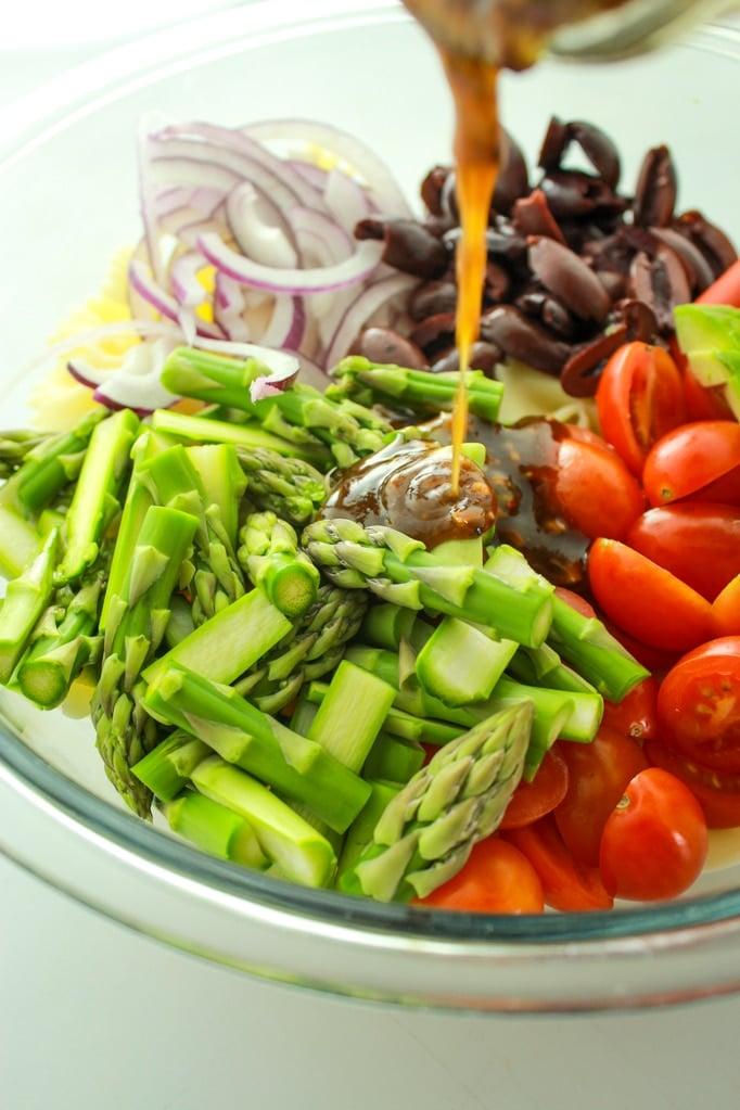 Vegan Pasta Salad Pouring Sauce into bowl