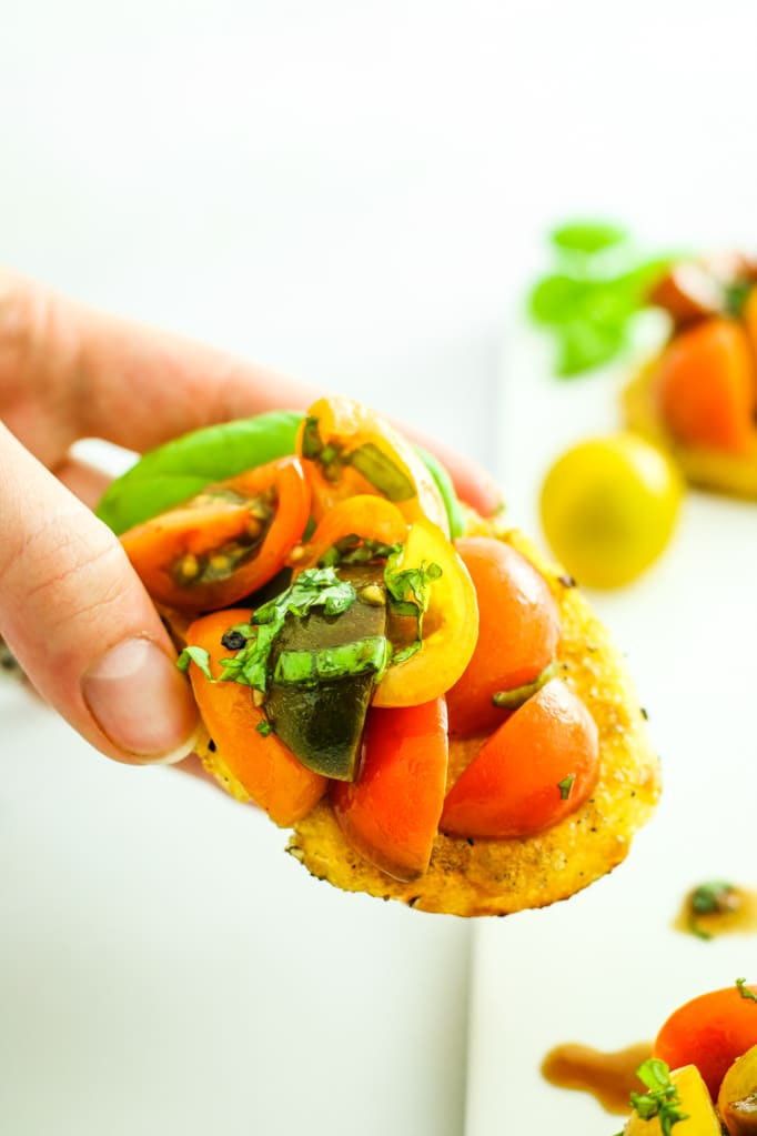 Grilled Polenta Bruschetta - Summer food perfection! These make the best appetizer or hors d'oeuvre. Made with fresh tomatoes and basil!