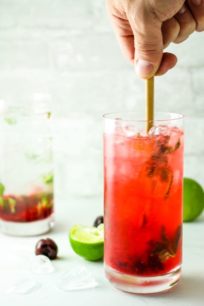 Black Cherry Mojitos in Glass Hand Stirring