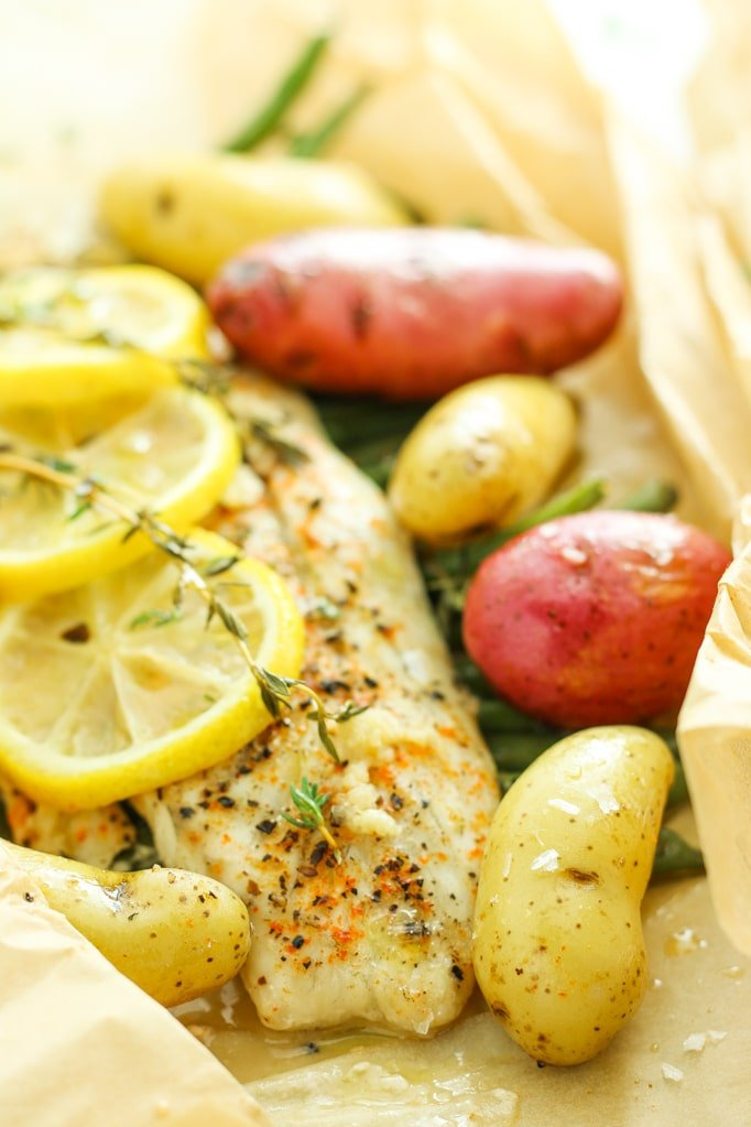 Parchment Pouch Fish Dinners with Fingerling Potatoes - New favorite way to cook fish. SO easy and tender. Wrap everything in parchment and pop it into the oven for an all-in-one dinner!