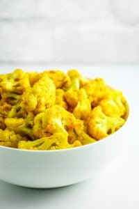 Turmeric Roasted Cauliflower - FAVORITE easy side dish. Toss everything in a bag, roast it, and you're done. I add this to my meal prep bowls all the time!