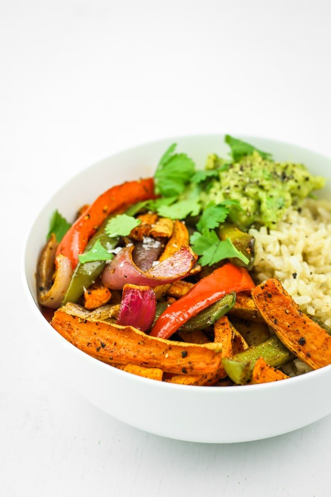 Sweet Potato Fajitas Meal Prep - This is EASY vegan meal prep. Veggies cook on a sheet pan and the rice gets done at the same time. My go to meal prep lately! Sweet potatoes and bell peppers!