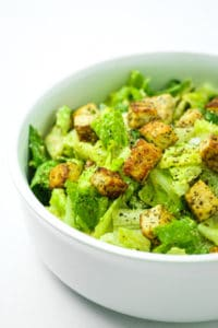 Vegan Caesar Salad with Tofu Croutons - This salad is SO GOOD. The dressing is actually better than non-vegan version of Caesar. The tofu bites get crispy and ALMOST seem like croutons. Non vegans can't even tell! Caesar dressing without parmesan or anchovies. #vegan #caesarsalad #nutritionalyeast #dressing