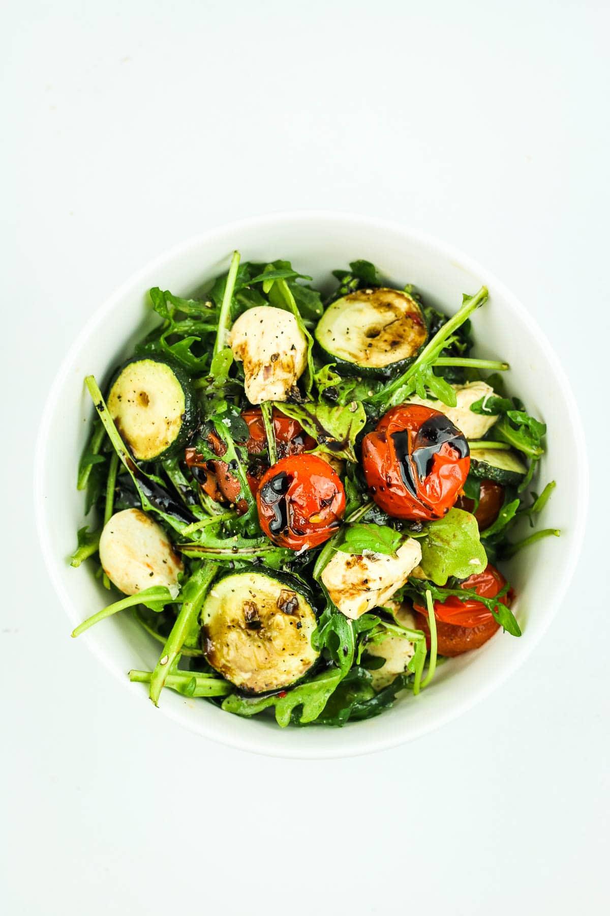 Grilled Zucchini Caprese Salad – SUMMER favorite. This caprese salad recipe has arugula, grilled tomatoes, grilled zucchini, and marinated mozzarella – plus a balsamic glaze. SO good. #salad #bbq #caprese #summer