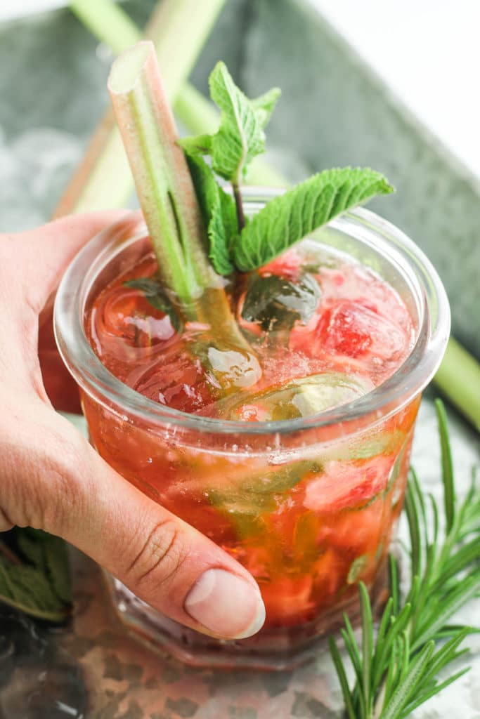 Strawberry Rhubarb Gin Smash - The BEST summer cocktail - it's such a refreshing drink. Made with gin, rhubarb simple syrup, strawberries, and mint. #cocktail #rhubarb #gin